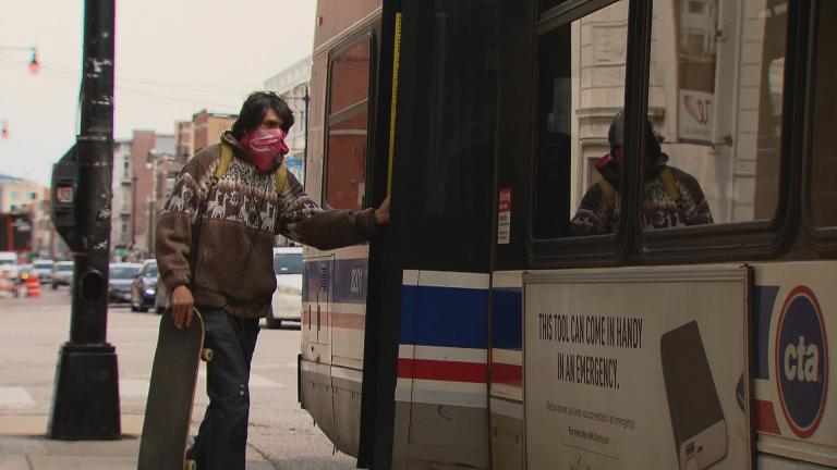 A passenger boards a CTA bus from the rear doors on Thursday, April 9, 2020. (WTTW News)