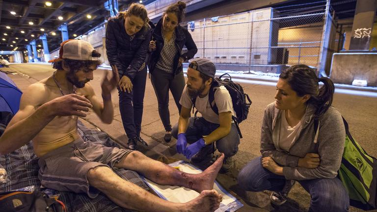 Members of Chicago Street Medicine deliver care to a man who is homeless. (Courtesy of Lloyd DeGrane Photography)