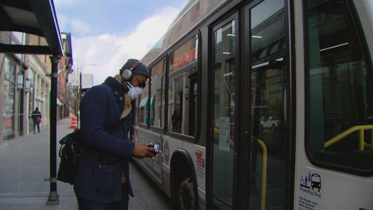 A person wearing a face mask boards a CTA bus in Chicago. (WTTW News)