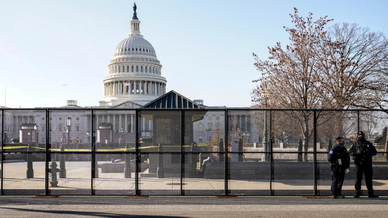 Capitol police officers stand outside of fencing that was installed around the exterior of the Capitol grounds, Thursday, Jan. 7, 2021 in Washington. (AP Photo / John Minchillo)