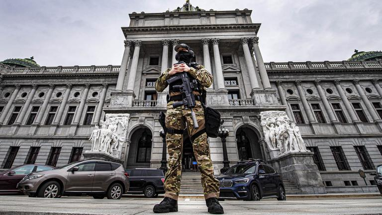 A member of the Pennsylvania Capitol Police stands guard at the entrance to the Pennsylvania Capitol Complex in Harrisburg, Pa., Wednesday, Jan. 13, 2021. (Jose F. Moreno / The Philadelphia Inquirer via AP)