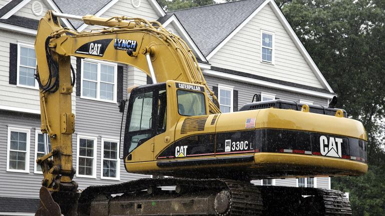 In this July 24, 2017 file photo, a Caterpillar excavator rests at a housing construction site in North Andover, Mass. Caterpillar Inc. reports earnings Tuesday, Oct. 23, 2018. (AP Photo / Elise Amendola, FIle)