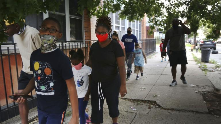 St. Francis Xavier School students and their families walk together in Newark, on Thursday, Aug. 6, 2020, after discussing the Catholic school's permanent closure announced the previous week by the Archdiocese of Newark. Nationwide, more than 140 Catholic schools will not reopen in the fall. (AP Photo/Jessie Wardarski)