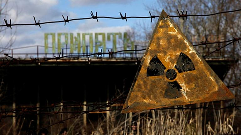 A radioactive sign hangs on barbed wire outside of a café in Pripyat, which is near the Chernobyl Power Plant. (Diana Markosian  / Wikimedia)