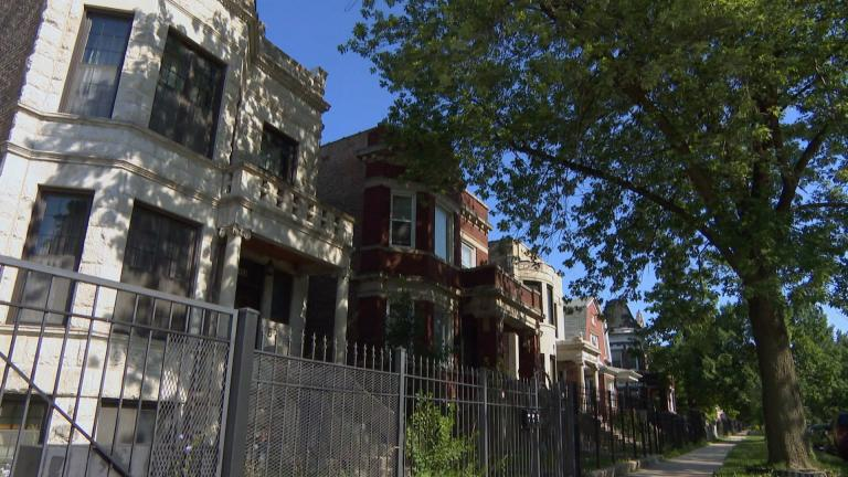 In this file photo, houses sit behind metal fencing on a tree-lined street in Chicago. (WTTW News)