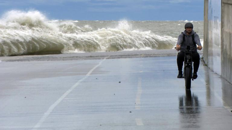 A man rides a bike along a wave-battered lakefront in Chicago on Wednesday, Sept. 22, 2021. (WTTW News)