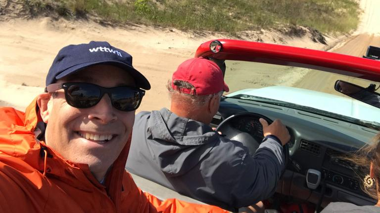 """Geoffrey Baer, host of """"Chicago on Vacation,"""" takes a selfie in a dune buggy in Silver Lake, Michigan, with Bob Collins behind the wheel."""