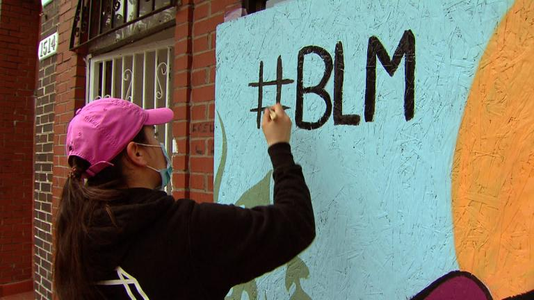 A woman paints a Black Lives Matter mural in Chicago. (WTTW News)