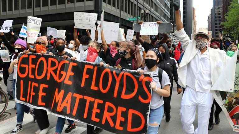 Protesters march along Dearborn Street while holding a sign honoring George Floyd on Saturday, May 30, 2020. Eric Russell, right, an activist with the Tree of Life Justice League, joins them. He also spoke at the protest. (Evan Garcia / WTTW News)