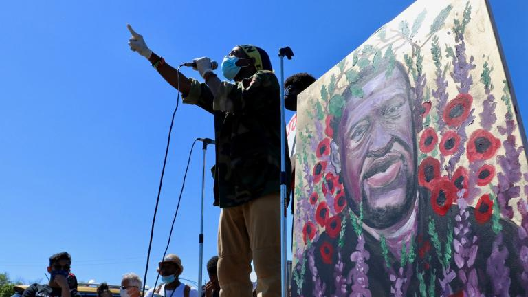 Standing before a painting of George Floyd, a speaker addresses the crowd in Seward Park on Saturday, June 6, 2020. (@EvanRGarcia / Twitter)