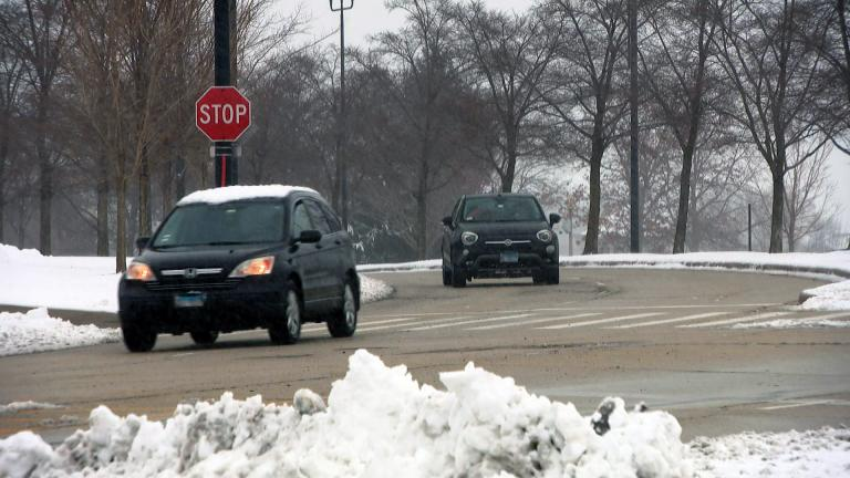 Cars drive on cleared roads in Chicago on Tuesday, Jan. 26, 2021 after the season's first big snowfall. The city is gearing up for another major storm on Saturday, Jan. 30. (WTTW News)