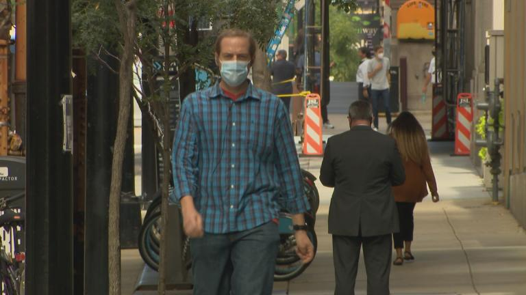 People wearing face masks walk along a street in downtown Chicago on Sept. 2, 2020. Officials concerned about the possibility for a spike in COVID-19 infections over the Labor Day weekend are reminding residents to wear masks and practice social distancing. (WTTW News)