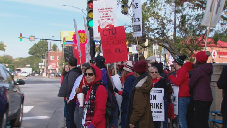 Chicago teachers hold signs and walk the picket line on day two of a strike on Friday, Oct. 18, 2019. (WTTW News)