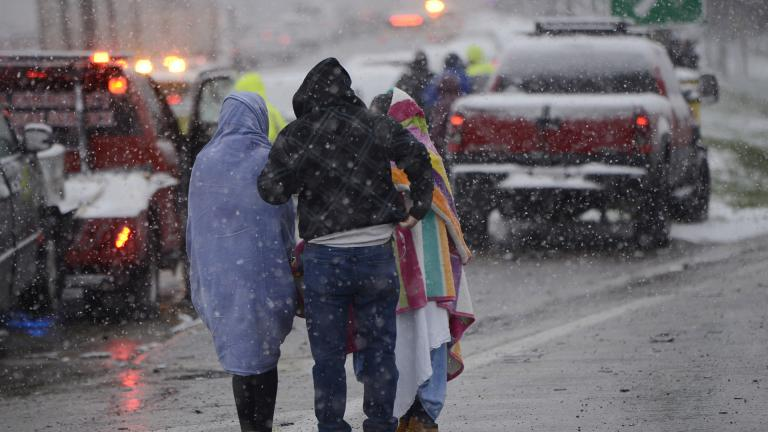 Motorists huddle together after a 54 car pile-up early morning on the Kennedy Expressway Wednesday, April 15, 2020, in Chicago. (AP Photo / Paul Beaty)