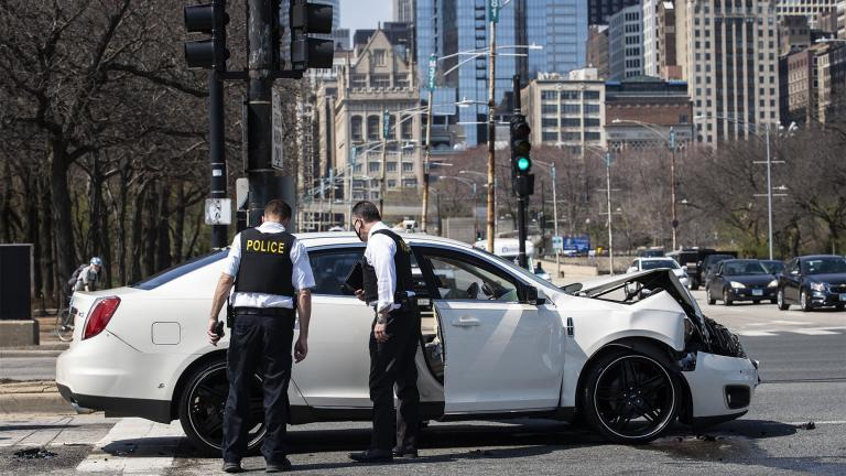 Chicago police investigate in the northbound lanes of Lake Shore Drive at East Monroe Street, where a 2-year-old boy was shot in the head while he was traveling inside a car near Grant Park, Tuesday, April 6, 2021. (Ashlee Rezin Garcia / Chicago Sun-Times via AP)