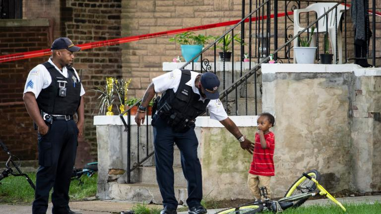 A Chicago police officer helps a child walk through an area being investigated after two men were shot Friday, July 3, 2020, in Chicago. (Ashlee Rezin Garcia / Chicago Sun-Times via AP)