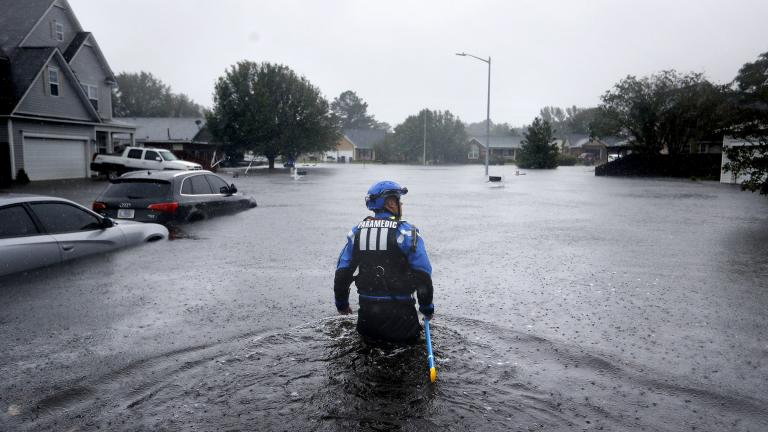 In this Sunday, Sept. 16, 2018 file photo, a member of the North Carolina Task Force urban search and rescue team wades through a flooded neighborhood looking for residents who stayed behind as Florence continues to dump heavy rain in Fayetteville, N.C. (AP Photo / David Goldman)
