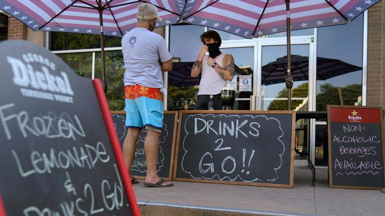 A drinks-to-go table is set up outside the Old Crow bar on Greenville Avenue in Dallas, Thursday, Aug. 13, 2020. Some states and cities in the U.S. are allowing cocktails to go due to the pandemic. (AP Photo / LM Otero)