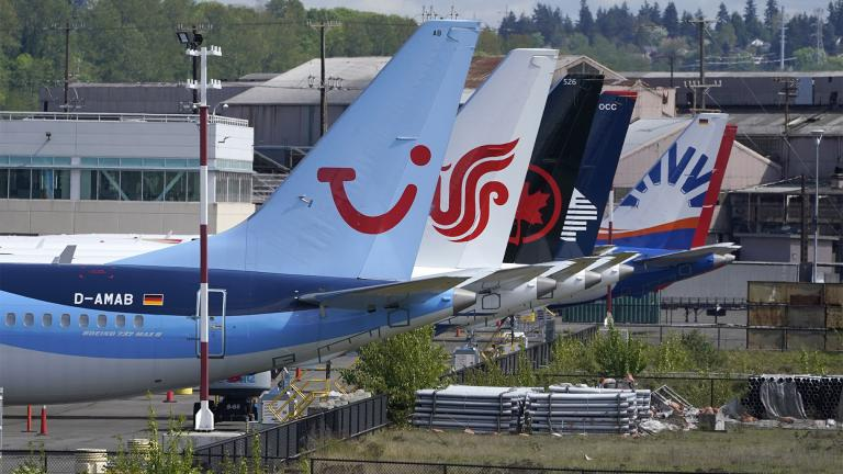 Boeing 737 Max airplanes, including one belonging to TUI Group, left, sit parked at a storage lot, Monday, April 26, 2021, near Boeing Field in Seattle. (AP Photo / Ted S. Warren)