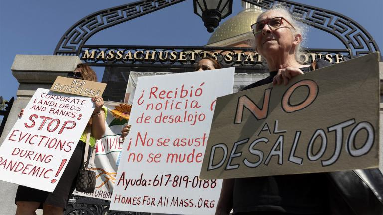 People from a coalition of housing justice groups hold signs protesting evictions during a news conference outside the Statehouse, Friday, July 30, 2021, in Boston. (AP Photo / Michael Dwyer)