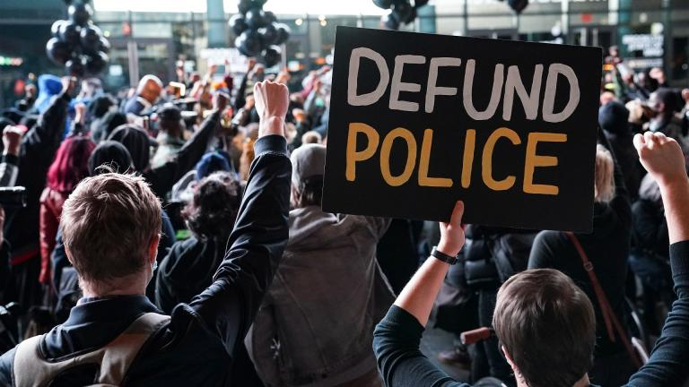 """In this Oct. 14, 2020, file photo a protester holds a sign that reads """"Defund Police"""" during a rally for the late George Floyd outside Barclays Center in New York. (AP Photo / John Minchillo, File)"""