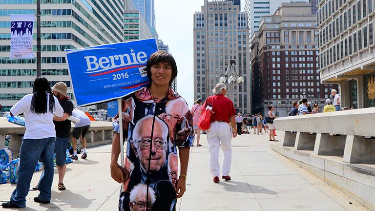 """Oscar Salazar, 21, wears full Bernie Sanders garb outside City Hall. """"Right now, [Hillary Clinton] doesn't deserve my vote,"""" Salazar said. """"She needs to show that she'll be continuing the progressive ideas of Bernie."""" (Evan Garcia / Chicago Tonight)"""