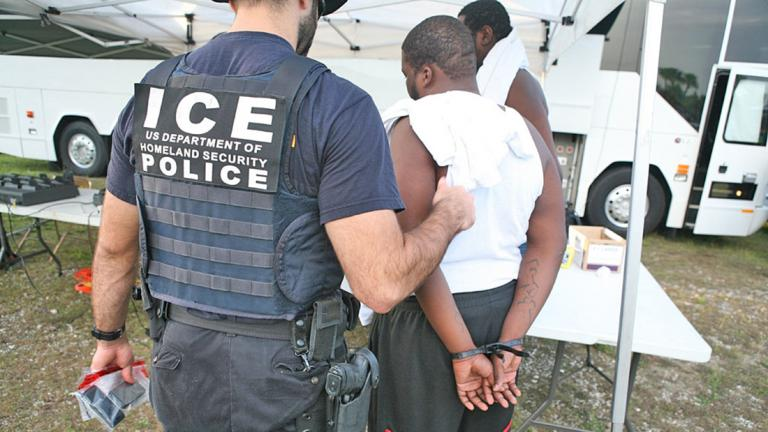 An ICE agent arrests a suspect.