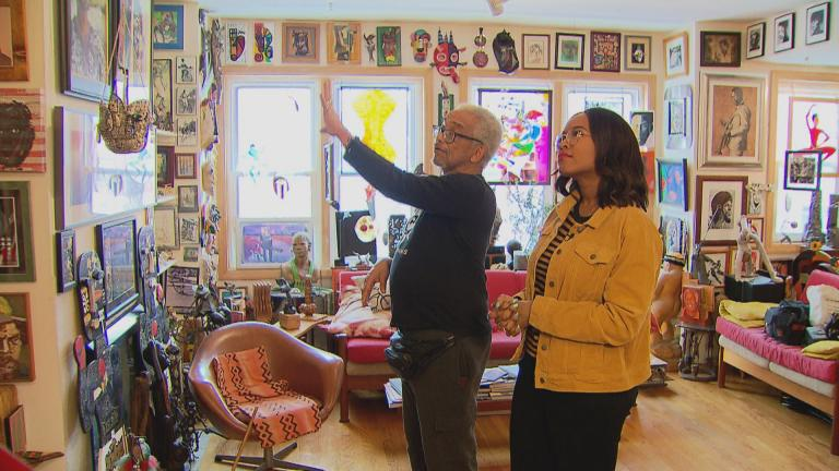 Patric McCoy shows WTTW arts correspondent Angel Idowu his art collection. (WTTW News)