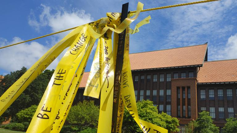 "Handwritten messages on yellow ribbon comprise the installation ""Dirty Laundry"" on the lawn at Carl Schurz High School. (Erica Gunderson / WTTW News)"