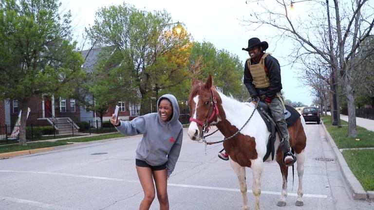 A young woman takes a photo with Adam Hollingsworth, also known as the Dreadhead Cowboy, and his 13-year-old horse Prince in the Woodlawn neighborhood on Chicago's South Side on Saturday, May 16. (Evan Garcia / WTTW News)