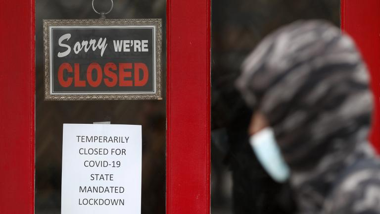 In this May 7, 2020, file photo, a pedestrian walks by The Framing Gallery, closed due to the COVID-19 pandemic, in Grosse Pointe, Michigan. (AP Photo / Paul Sancya, File)