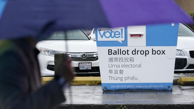 A pedestrian walks past a King County ballot drop box, closed until ballots are mailed about three weeks before the election, on a Seattle street Thursday, Sept. 24, 2020. (AP Photo / Elaine Thompson)