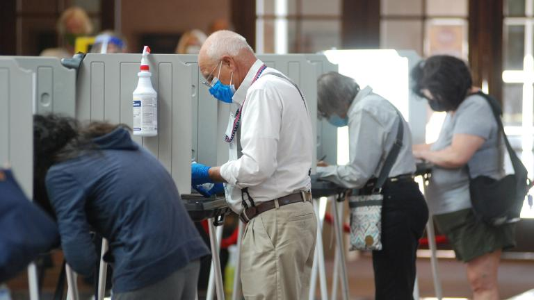 Temporary election worker Joseph Banar, center, disinfects voting stations as a precaution against the coronavirus while a steady stream of voters participates in the first day of balloting in New Mexico, at the Santa Fe Convention Center on Tuesday, Oct. 6, 2020, in Santa Fe, N.M. (AP Photo / Morgan Lee)