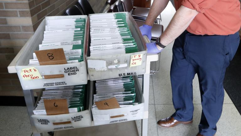 In this May 5, 2020, file photo, absentee ballots to be counted are moved at City Hall in Garden City, Mich. Data obtained by The Associated Press shows Postal Service districts across the nation are missing the agency's own standards for on-time delivery as millions of Americans prepare to vote by mail. (AP Photo/Paul Sancya, File)