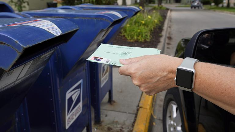In this Tuesday, Aug. 18, 2020, file photo, a person drops applications for mail-in-ballots into a mail box in Omaha, Neb. (AP Photo / Nati Harnik, File)