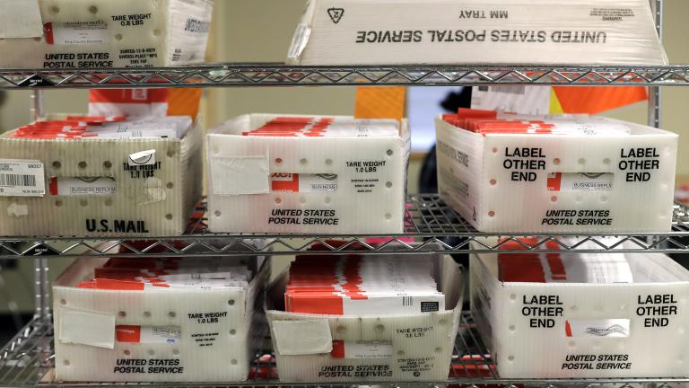 In this Aug. 5, 2020, file photo vote-by-mail ballots are shown in U.S. Postal service sorting trays the King County Elections headquarters in Renton, Wash., south of Seattle. (AP Photo / Ted S. Warren, File)