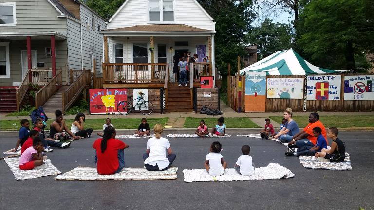 Participants take part in street yoga outside the Peace House, a community center in Englewood built by the nonprofit group I Grow Chicago. (Courtesy of Erin Vogel)