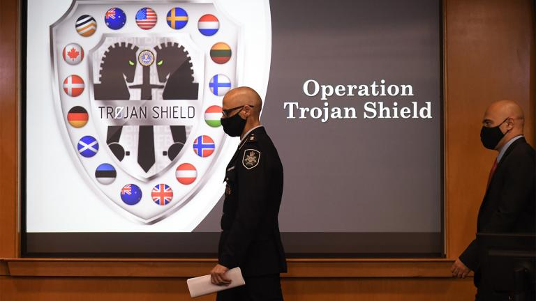 Law enforcement officials walk past an Operation Trojan Shield logo at a news conference, Tuesday, June 8, 2021, in San Diego. (AP Photo / Denis Poroy)