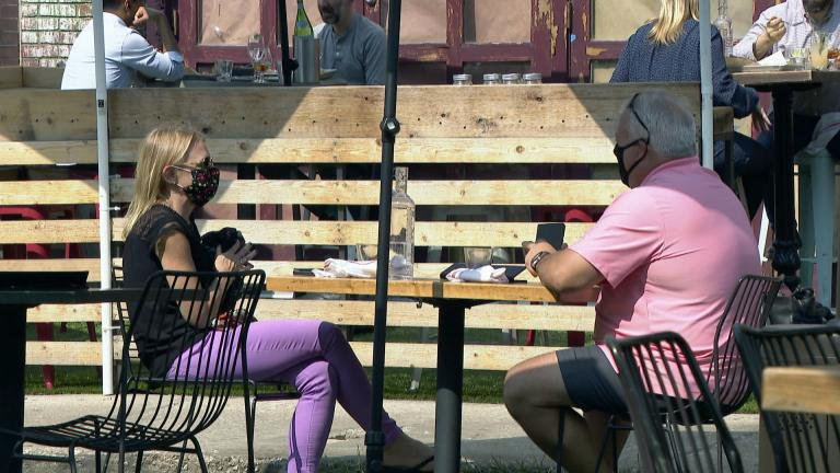 Diners wear face masks as they sit outside a restaurant in Chicago. (WTTW News)