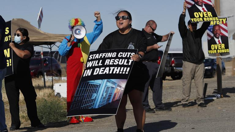 Noni Ahulau, from Honolulu, along with others, protests staffing shortages at the Federal Correctional Institution at Mendota, Monday, May 17, 2021, near the facility, in Mendota, Calif. The signs being displayed and held, at right, show a picture of FCI Mendota Warden Douglas K. White. (AP Photo / Gary Kazanjian)