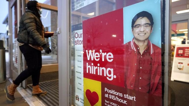 In this Feb. 9, 2021 file photo, a passer-by walks past an employment hiring sign while entering a Target store location, in Westwood, Mass. (AP Photo/Steven Senne, File)