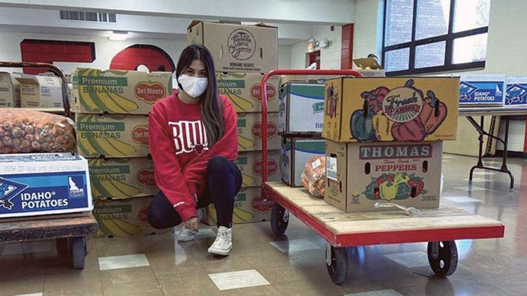 Elizabeth Morales, founder of Del Dia Chicago, sits with boxes of fresh produce she gets every week from farmers. (Courtesy Elizabeth Morales)
