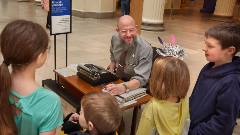 Eric Elshtain, the Field Museum's first-ever poet-in-residence, interacts with a group of children in the museum's Stanley Field Hall. (John Weinstein / The Field Museum)