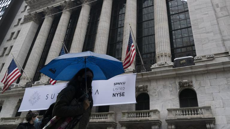 A woman with an umbrella passes the New York Stock Exchange, Monday, Oct. 26, 2020. (AP Photo / Mark Lennihan)
