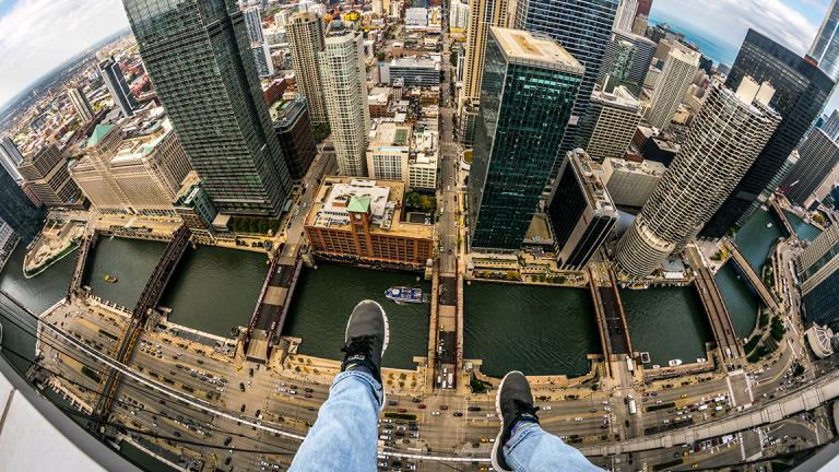 "A self-described ""rooftopper"" dangles his feet, a familiar perspective for such photographers, while sitting atop a Chicago skyscraper. (Courtesy Andrew Fitzsimmons)"