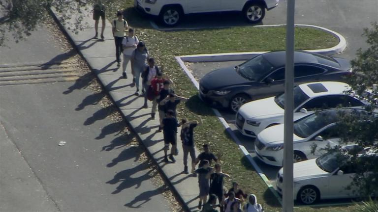 Students are evacuated from Marjory Stoneman Douglas High School on Feb. 14, 2018 after a gunman opened fire.