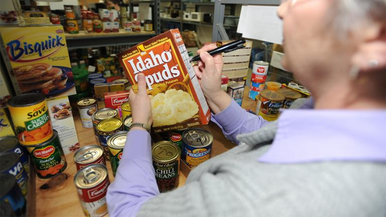 A staff member stocks the shelves of the food pantry at the Airman Family Readiness Center at Whiteman Air Force Base in Missouri. (U.S. Air Force photo By Airman 1st Class Carlin Leslie)