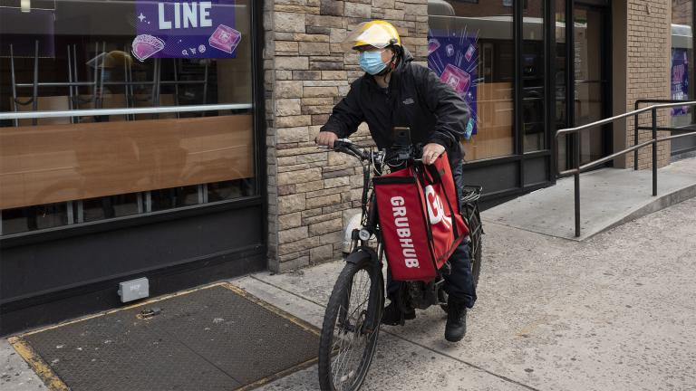 In this April 21, 2021 file photo, a delivery man bikes with a food bag from Grubhub in New York. (AP Photo / Mark Lennihan, File)