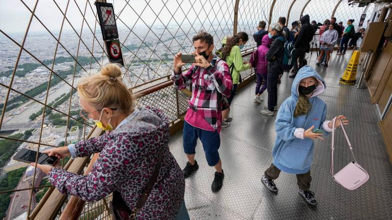 In this Friday, July 16, 2021 file photo, visitors enjoy the view from top of the Eiffel Tower in Paris. (AP Photo / Michel Euler, File)