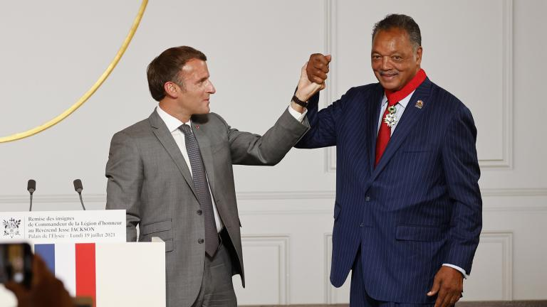 French President Emmanuel Macron, left, and Reverend Jesse Jackson raise their hands after Jackson was awarded with the Legion d'Honneur (Officer of the Legion of Honor) medal during a ceremony at the Elysee Palace in Paris, Monday, July 19, 2021. (Ludovic Marin / Pool Photo via AP)